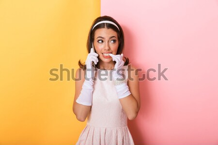 Attractive smiling pinup girl in yellow dress pointing up Stock photo © deandrobot