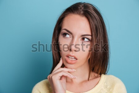 Close-up portrait of pensive girl thinking over blue background Stock photo © deandrobot