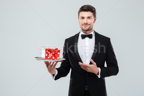 Waiter in tuxedo standing and holding present box on tray Stock photo © deandrobot