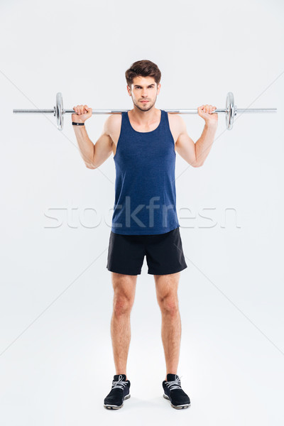 Concentrated young sportsman standing and working out with barbell Stock photo © deandrobot