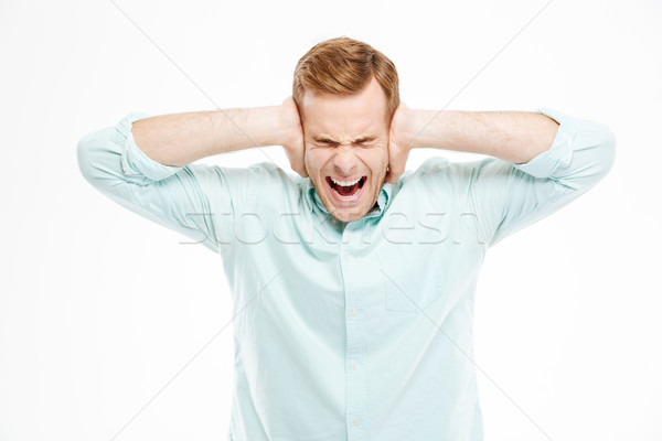 Stock photo: Irritated stressed young man covered ears by hands and shouting