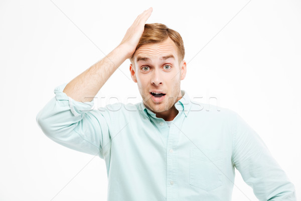 Portrait of surprised handsome young businessman with mouth opened Stock photo © deandrobot