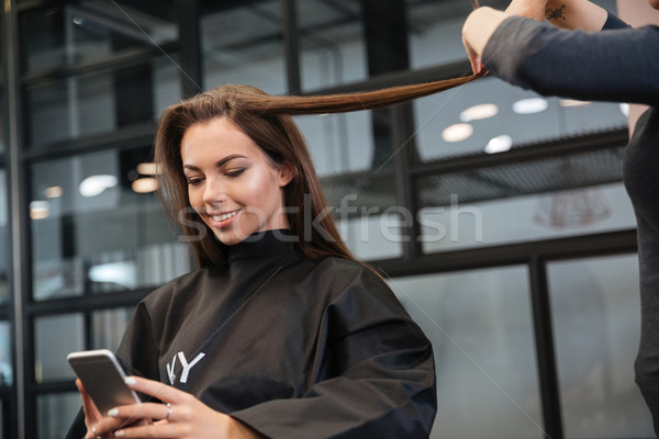 Woman with smartphone and hairdresser making hair styling at salon Stock photo © deandrobot