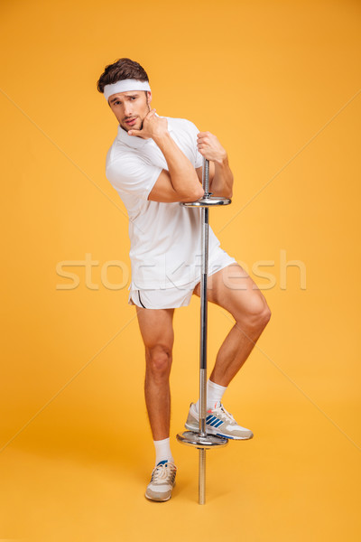 Handsome young fitness man posing with barbell Stock photo © deandrobot