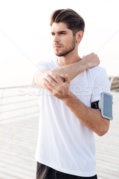 Man athlete with mobile phone in armband stretching arms Stock photo © deandrobot
