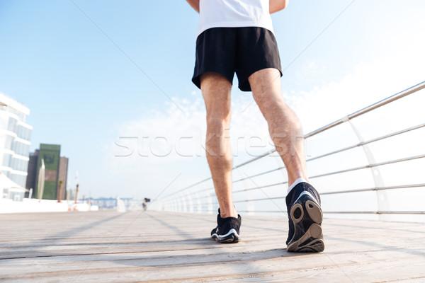 Nogi młody człowiek czarny uruchomiony molo Zdjęcia stock © deandrobot