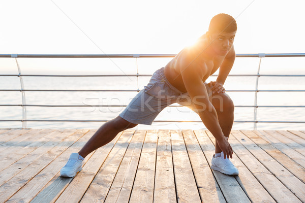 Handsome shirtless african man exercising and stretching legs Stock photo © deandrobot
