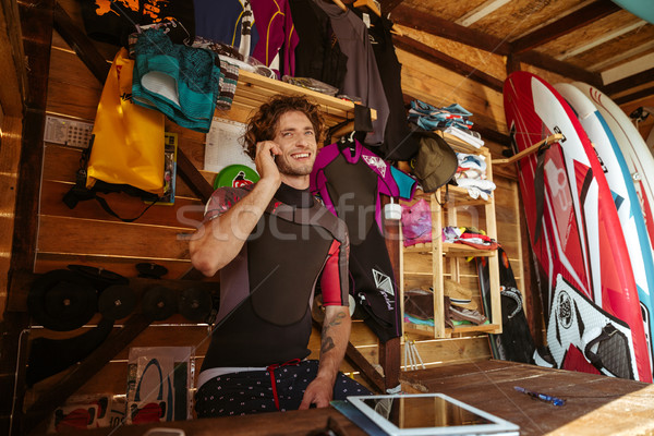 Man in swimsuit talking on smartphone in the surf shack Stock photo © deandrobot