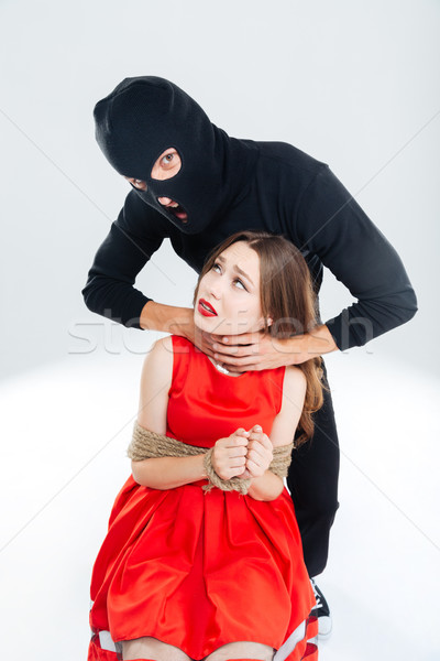 Scared woman bounded with ropes choking by man in balaclava Stock photo © deandrobot