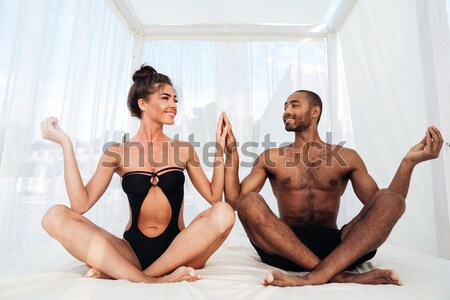 Couple mediating and sitting in lotus position on the beach Stock photo © deandrobot