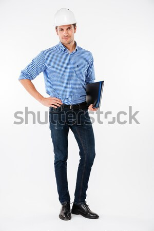 Confident man builder in hard hat standing and holding folder Stock photo © deandrobot
