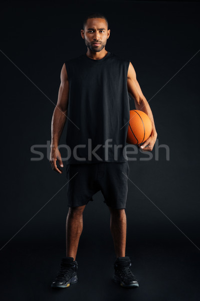 Concentrated serious african sports man holding basket ball Stock photo © deandrobot