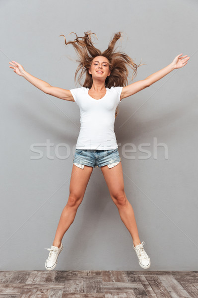 Portrait of a joyful woman jumping with hands up Stock photo © deandrobot