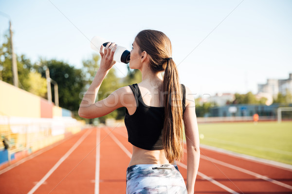 Young female athlete drinking from water bottle after workout outdoors Stock photo © deandrobot