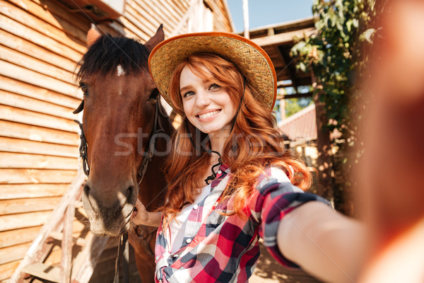 Happy woman cowgirl taking selfie with her horse on ranch Stock photo © deandrobot