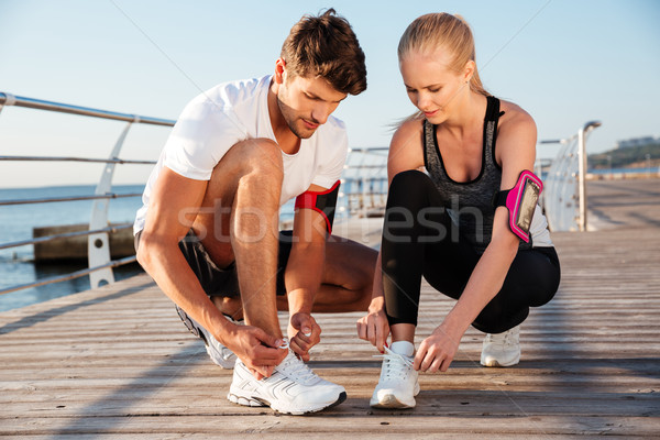 Smiling couple tying shoelaces outdoors Stock photo © deandrobot