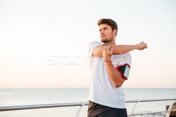 Young muscular man stretching his arms outdoors Stock photo © deandrobot