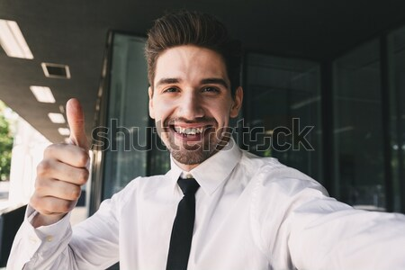 Happy young businessman talking on mobile phone near business center Stock photo © deandrobot