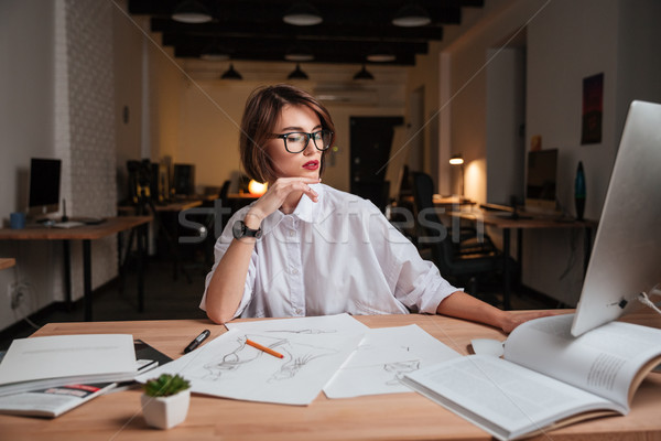 Attractive young woman fashion designer sitting and working in office Stock photo © deandrobot