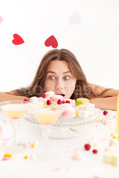Surprised woman looking at holiday table with cakes and sweets Stock photo © deandrobot