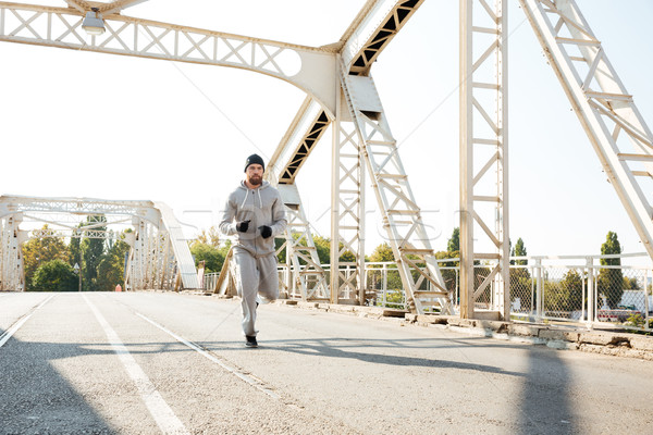 Stock photo: Concentrated sports man jogging across the bridge in the morning