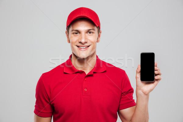 улыбаясь курьер телефон студию смартфон Сток-фото © deandrobot