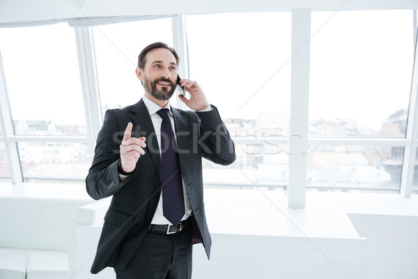 Elderly bearded business man talking at phone in office Stock photo © deandrobot