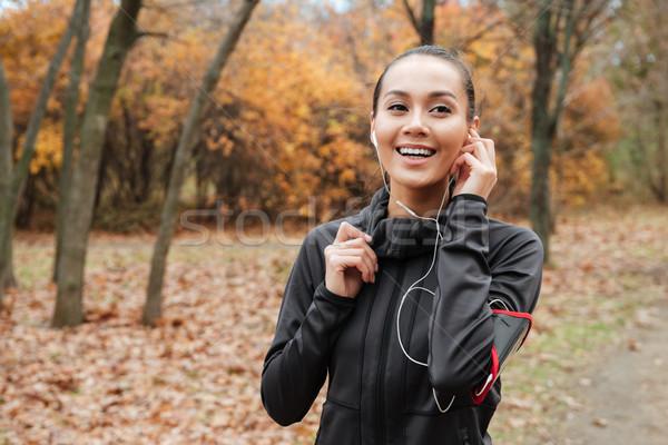 Derűs hölgy futó fülhallgató ősz park Stock fotó © deandrobot