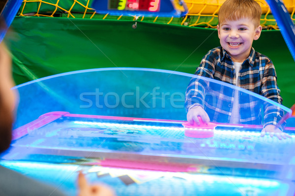 Cheerful little boy playing air hockey at indoor playground Stock photo © deandrobot