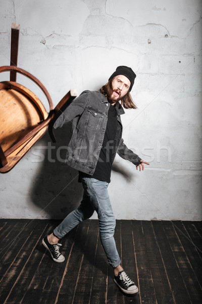 Bearded hipster man in hat throwing chair at camera Stock photo © deandrobot