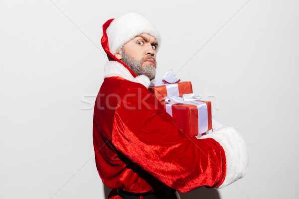 Angry frowning man santa claus holding gift boxes Stock photo © deandrobot