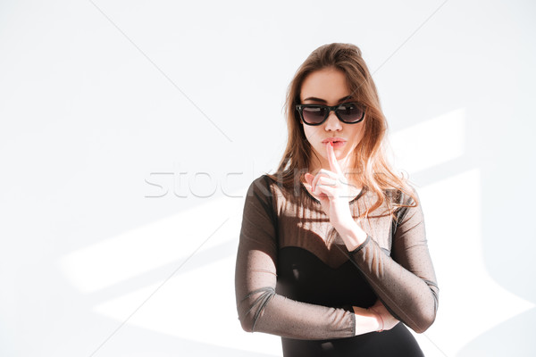 Gorgeous lady wearing sunglasses make silence gesture Stock photo © deandrobot