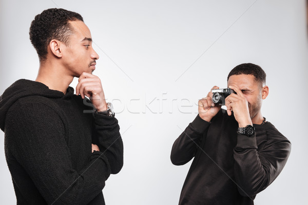 Attractive african men make a photo with camera. Stock photo © deandrobot