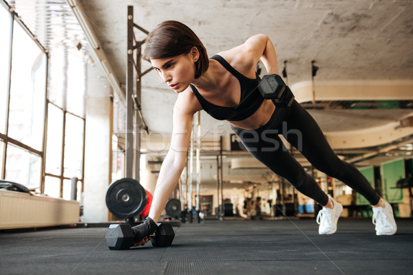 Woman athlete doing exercises with dumbbells in gym Stock photo © deandrobot
