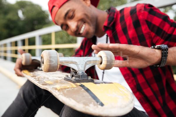 Happy dark skinned guy wearing cap looking on his skateboard Stock photo © deandrobot