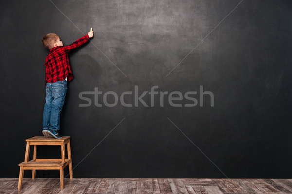 Child standing on stool over chalkboard and drawing at board Stock photo © deandrobot