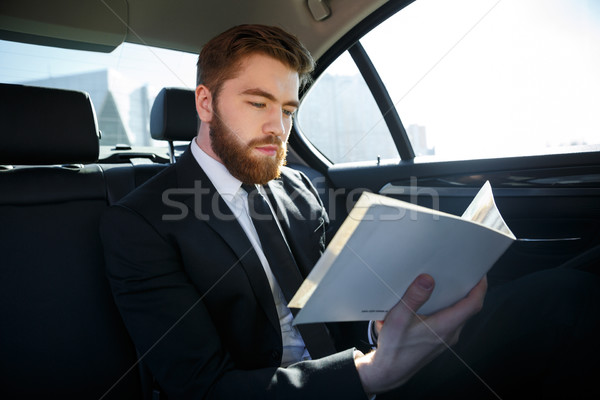Concentrated young businessman analyzing documents while traveling Stock photo © deandrobot