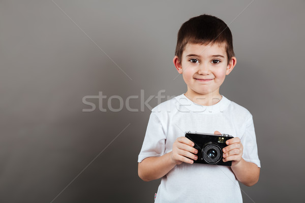 Happy little boy standing and holding photo camera Stock photo © deandrobot
