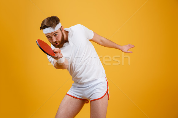 Handsome young sportsmand holding racket for table tennis. Stock photo © deandrobot