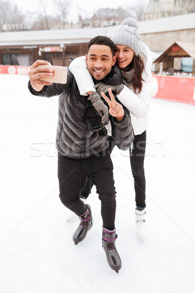 Cheerful loving couple skating at ice rink outdoors make selfie Stock photo © deandrobot