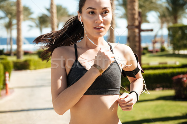 Sportswoman running and listening to music with earphones in summer Stock photo © deandrobot