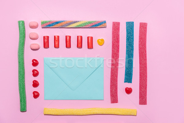 Photo of blank paper envelope with colorful sweet sugar candies Stock photo © deandrobot