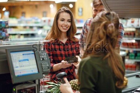 Stock photo: Happy young lady standing near cashier's desk