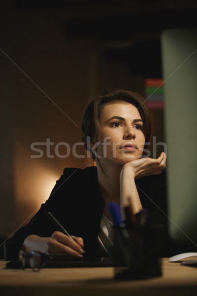 Concentrated young lady designer sitting in office at night Stock photo © deandrobot