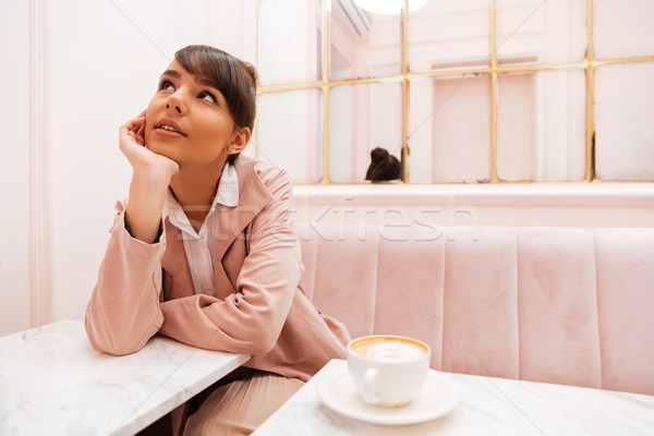 Pretty young woman sitting and looking away at cafe table Stock photo © deandrobot
