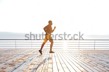 Concentrated young sportsman make sport exercises with ball Stock photo © deandrobot