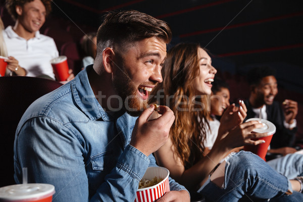 Laughing friends sitting in cinema watch film Stock photo © deandrobot