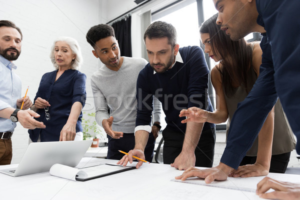 Group of businesspeople working at a table in the office Stock photo © deandrobot