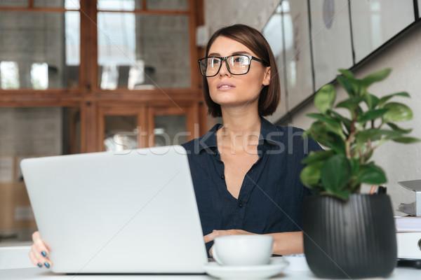 Dalgın kadın gözlük çalışma dizüstü bilgisayar tablo Stok fotoğraf © deandrobot