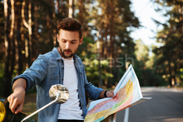 Bearded man near scooter looking at map outdoors. Stock photo © deandrobot